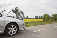 A person in a radiation protective suit looking under the hood of a car  11016030871| 写真素材・ストックフォト・画像・イラスト素材|アマナイメージズ
