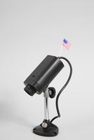 Close-up of security camera with American flag against white background