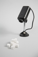 Security camera and sugar cubes against white background