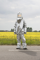 A person in a radiation protective suit standing in front of an oilseed rape field 11016030880| 写真素材・ストックフォト・画像・イラスト素材|アマナイメージズ