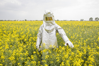 A person in a radiation protective suit standing in an oilseed rape field 11016030884| 写真素材・ストックフォト・画像・イラスト素材|アマナイメージズ