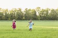Girls running on grassy field