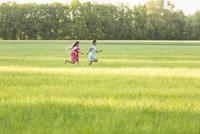 Side view of girls running on grassy field