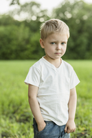 Portrait of cute boy standing with hand in pocket on field