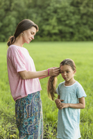 Mother making daughter's hair on field