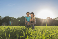 Mother and daughter sitting on grassy field