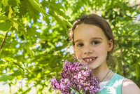 Portrait of happy girl holding purple flowers outdoors