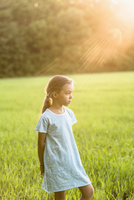 Thoughtful girl standing on grassy field