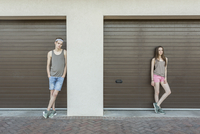 Young man and woman leaning against closed garage