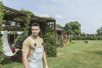 Young man wearing bib overalls in backyard