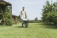 Young man walking with wheelbarrow in backyard