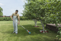 Full length of young man with rake cleaning lawn