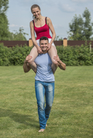 Full length portrait of happy young man carrying woman on shoulders in backyard