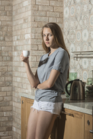 Portrait of beautiful young woman having coffee while leaning on kitchen counter