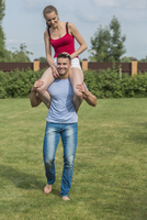 Full length of happy young man carrying woman on shoulders in backyard