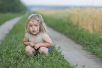 Portrait of cute girl crouching on plants