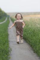 Full length portrait of happy little girl walking on nature trail