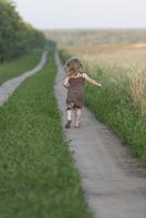 Full length rear view of little girl walking on nature trail