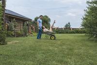 Full length of man pushing girlfriend in wheelbarrow at backyard