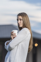 Beautiful young woman holding coffee cup outdoors