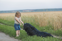 Girl playing with dog on field
