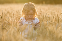 Girl standing amidst wheat field