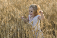 Happy girl walking in wheat field