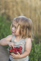 Cute girl holding bowl full of strawberries outdoors