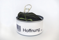 Open tin can with seedling, German word for hope, Hoffnung, on label