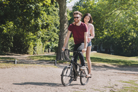 Full length of young couple riding bicycle at park