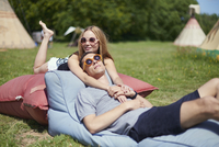 Young couple lying on pillows while glamping, teepee in background