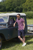 Full length of young man leaning on jeep in park