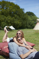 Loving couple lying on pillows while glamping, teepee in background
