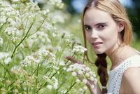 Portrait of beautiful woman by flower plants in park