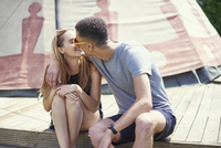 Young couple kissing on teepee structure while glamping