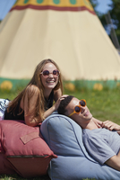 Happy couple lying on pillows while glamping, teepee in background