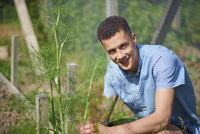 Portrait of handsome young man sitting at plant nursery