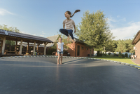 Girl with sister jumping on trampoline in yard