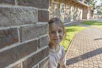 Portrait of smiling girl by brick wall