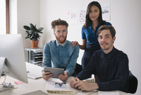 Portrait of confident business people at desk in office