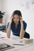 Young businesswoman suffering from headache at desk