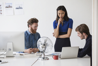 Young business coworkers discussing at desk