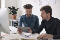 Young businessmen using digital tablet together at desk
