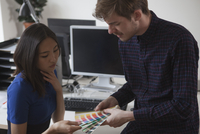 Young male and female business colleagues choosing color from swatches in office