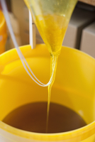 Close-up of fresh honey being poured in container