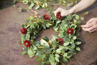 Cropped hand making wreath outdoors