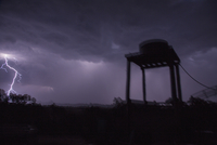 Low angle view of silhouette water tank against sky during stormy weather