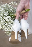 Cropped image of bride holding high heels and flowers