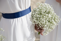 Midsection of bride holding flowers outdoors