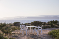 Chairs and table on beach against clear sky